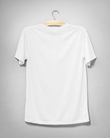 Weißes Hemd, das an der Zementwand hängt. Leere Kleidung für Design. Rückansicht.
