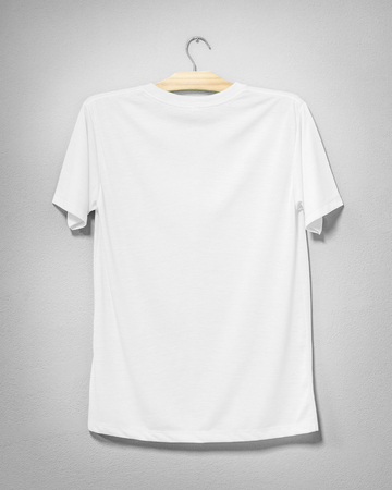 White shirt hanging on cement wall. Empty clothing for design. Back view.