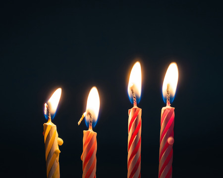 Burning birthday candles on dark background with fire. Stock Photo