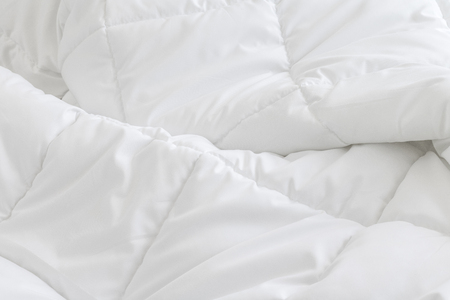 White bedding sheets background. Messy bed concept.