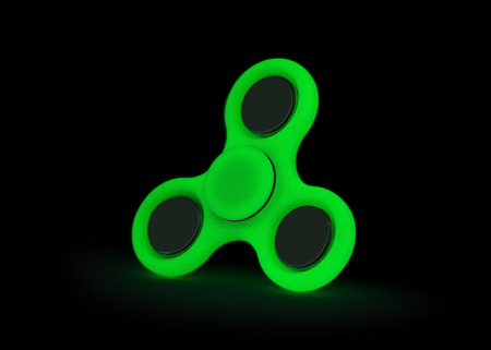 Glow in the dark. Green fidget spinner isolated on white background. Stress relieving toy. Stock Photo
