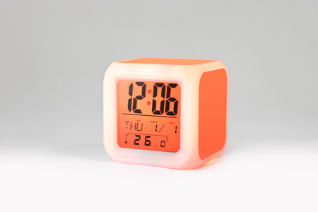 Modern alarm clock on white backdrops and copyspace. LED light or digital display. Фото со стока