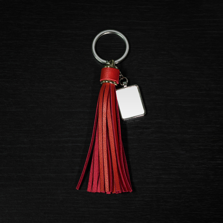 Red Leather Tassel key ring on black wooden background. Fashion leather key chain for decoration.