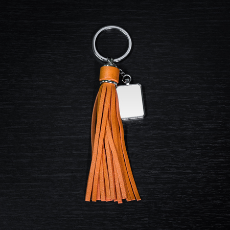 Colorful Leather Tassel key ring on black wooden background. Fashion leather key chain for decoration.
