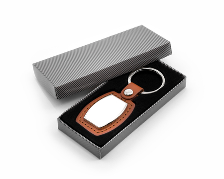Leather key ring on white background. Fashion key chain in package box. Souvenir or accessories. Imagens