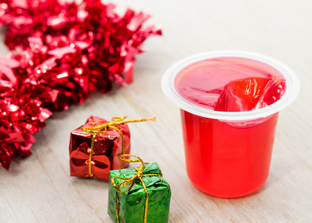 Delicious strawberry jelly and xmas gift box on wooden table. Sweet fruity pudding in transparent cup.