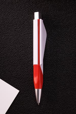 Dark pen and white card on dark background. Blank ballpoint pen for your design.