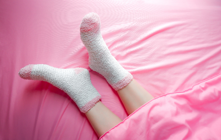 Women wearing socks in winter morning and blankets background. Warm and cozy on bedding sheet.