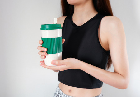 Woman holding a coffee cup in hands with exercises girls background. Blank mug for design. Stok Fotoğraf