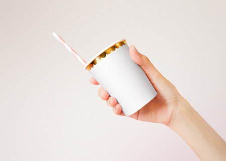Hand holding Paper Cup with straws on background. Template of blank Mug for design.