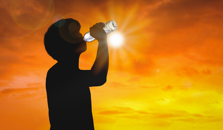 Silhouette man is drinking water bottle on hot weather background with summer season. High temperature and heat wave concept.