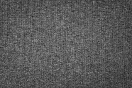 Grauer Baumwollbeschaffenheitshintergrund. Detail der Oberfläche des Pulloverstoffs.