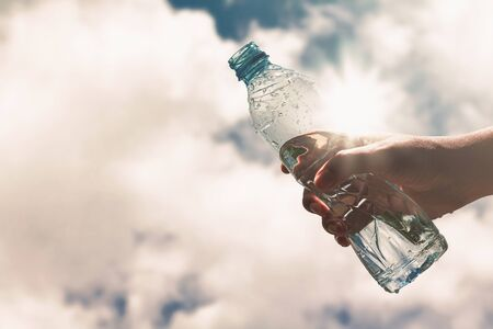 Hand holding a clear plastic bottle of pure drinking water refreshing and splash on a hot background with a hungry and thirsty concept for good health.
