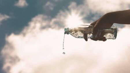 Pouring a clear plastic bottle of pure drinking water refreshing and splash on a heat wave background with a hungry and thirsty concept for good health. Stockfoto