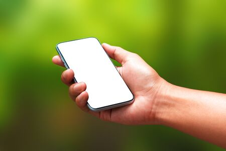 Hand holding a smartphone and an empty screen for your design on a natural green background in the morning concept. Mobile phone template has a blank screen for advertising. ( Clipping path screen ) Stockfoto