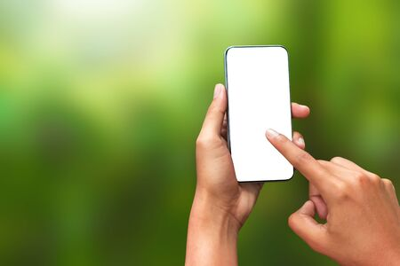 Hand touching a smartphone and an empty screen for your design on a natural green background in the morning concept. Mobile phone template has a blank screen for advertising. ( Clipping path screen )