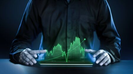 Business man showing profitable stock market holographic technology graphs in modern work background for the future. Company managers in concept planning and managing global marketing and investment. Stockfoto