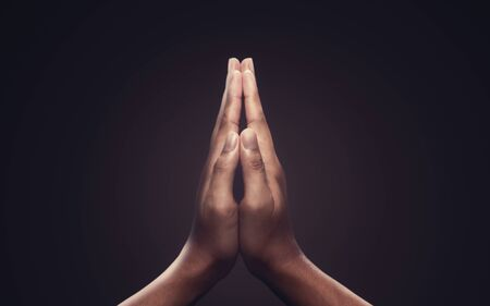 Praying hands with faith in religion and belief in God on dark background. Power of hope or love and devotion. Namaste or Namaskar hands gesture. Stockfoto
