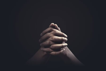 Praying hands with faith in religion and belief in God on dark background. Power of hope or love and devotion.