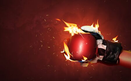 Old red boxing gloves on hot sparkles background with extreme fire flame and fighting fiercely hand for winner or success concept. Stockfoto