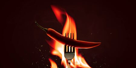 Red chilli peppers with a fork on a fire element and hot background. Spicy food and burning concept. Explosion of paprika chili tasty.