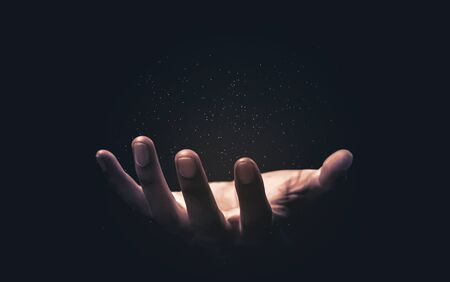 Praying hands with faith in religion and belief in God on blessing background. Power of hope or love and devotion. Magic powder floating on the magician hand.