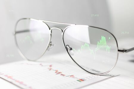 Working glasses of business man showing profits and graph of stocks on optical lens screen. Virtual reality glasses show the effect of a growing economy in terms of money and economics.