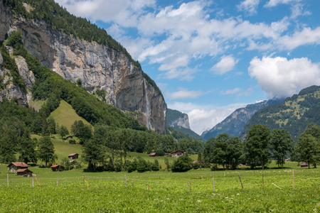 View valley of waterfalls in city Lauterbrunnen, Switzerland, Europe. Summer landscape, sunshine weather, dramatic blue sky and sunny day