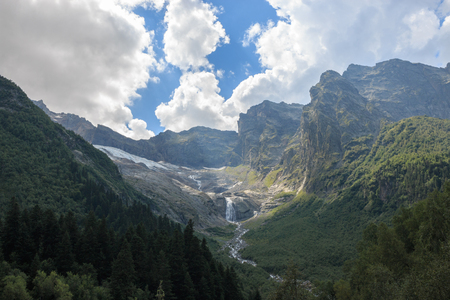 Closeup view mountains scenes and far away waterfall in national park Dombai, Caucasus, Russia, Europe. Summer landscape, sunshine weather and sunny day 写真素材