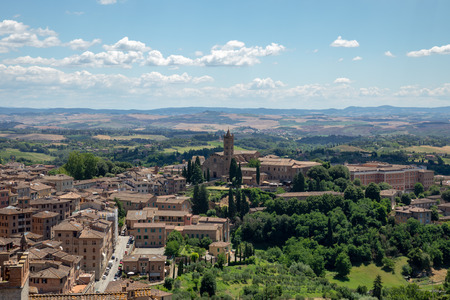 Panoramic view of Siena city with historic buildings and far away green fields from Siena Cathedral (Duomo di Siena). Summer sunny day and dramatic blue sky Stockfoto