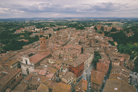 Panoramic view of Siena city with historic buildings and far away green fields from Torre del Mangia is a tower in city. Summer sunny day and dramatic blue sky Stockfoto