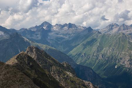 Panorama der Bergszene mit dramatischem bewölktem Himmel im Nationalpark von Dombay, Kaukasus, Russland. Sommerlandschaft und sonniger Tag