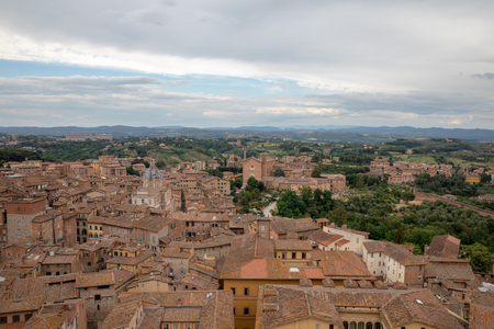 Panoramic view of Siena city with historic buildings and far away green fields from Torre del Mangia is a tower in city. Summer sunny day and dramatic blue sky 免版税图像