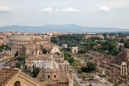 Panoramic view of city Rome with Roman forum and Colosseum from Vittorio Emanuele II Monument also known as the Vittoriano. Summer sunny day and dramatic blue sky