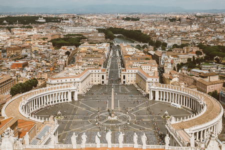 Rome, Italy - June 22, 2018: Panoramic view on the St. Peters Square and city of Rome from Papal Basilica of St. Peter (St. Peters Basilica). Summer day and people walk on square Editorial