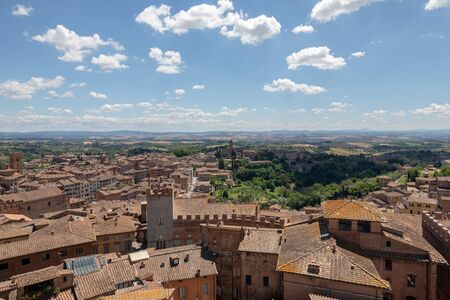 Panoramic view of Siena city with historic buildings and far away green fields from Siena Cathedral (Duomo di Siena). Summer sunny day and dramatic blue sky 免版税图像