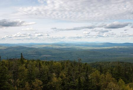 Panorama of mountains scenes in national park Kachkanar, Russia, Europe. Cloudy weather, dramatic blue color sky, far away green trees