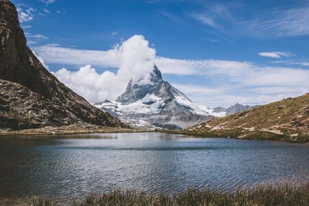 Panorama of Riffelsee lake and Matterhorn mountain, scene in national park Zermatt, Switzerland, Europe. Summer landscape, sunshine weather, dramatic blue sky and sunny day Stock Photo
