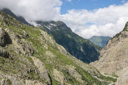 Panorama of mountains scene on route of Trift Bridge in national park Switzerland, Europe. Dramatic cloudy sky and sunny summer landscape