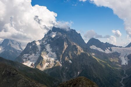 Panorama of misty mountains scene with dramatic blue sky in national park of Dombay, Caucasus, Russia. Summer landscape and sunny day