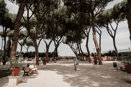 Rome, Italy - June 23, 2018: Panoramic view of Orange Garden (Giardino degli Aranci) on Aventino Hill. People walk and rest in national park of Rome. Summer day and blue sky