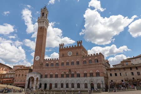 Siena, Italy - June 28, 2018: Panoramic view of Palazzo Pubblico (town hall) is a palace and Torre del Mangia is a tower in city on Piazza del Campo. Summer sunny day and dramatic blue sky