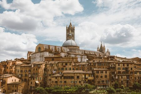 Panoramic view of Siena city with historic buildings and far away Siena Cathedral (Duomo di Siena). Summer sunny day and dramatic blue sky Stockfoto