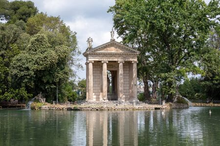 Panoramic view of Temple of Asclepius (Tempio di Esculapio) and lake in public park of Villa Borghese. Summer day and blue sky