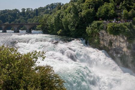 The Rhine Falls is the largest waterfall in Europe in Schaffhausen, Switzerland. Summer landscape, sunshine weather, blue sky and sunny day Banco de Imagens