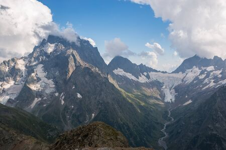Panorama of mountains scene with dramatic blue sky in national park of Dombay, Caucasus, Russia. Summer landscape and sunny day