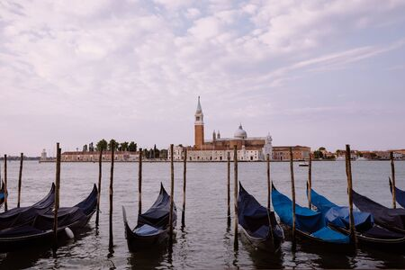 Panoramic view of Laguna Veneta of Venice city with gondolas and away San Giorgio Maggiore Island. Landscape of summer morning day and dramatic blue sky