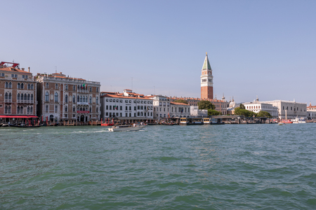 Venice, Italy - July 1, 2018: Panoramic view of Grand Canal (Canal Grande) with active traffic boats. It is a major water-traffic corridors in Venice city. Landscape of summer sunny day and blue sky