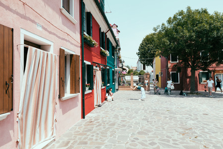 Burano, Venice, Italy - July 2, 2018: Panoramic view of brightly coloured homes of Burano is an island in the Venetian Lagoon. People walk and rest on streets. Summer sunny day and blue sky Redactioneel