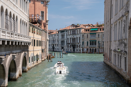 Venice, Italy - July 1, 2018: Panoramic view of Venice narrow canal with historical buildings and boats traffic from Bridge Foscari. Landscape of summer sunny day and blue sky Redactioneel